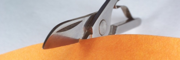 Scissors cutting orange paper
