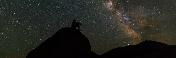 silhouette of person on rock, milky way in background
